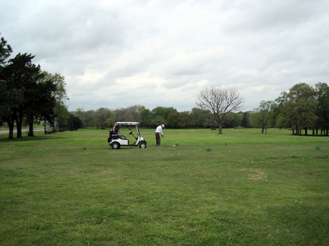 Golfer prepares for round on driving range