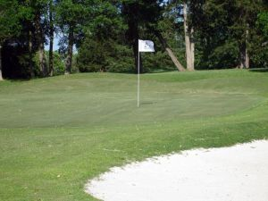 Flag blows in the wind on green with bunker in front