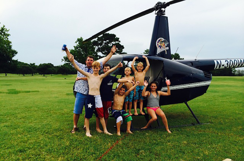 Kids pose in front of helicopter